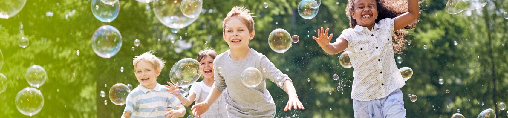 children running through bubbles
